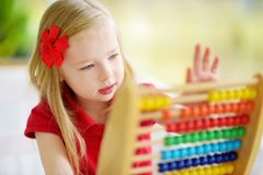 Cute little girl playing with abacus at home. Smart child learning to count. Cute little girl playing with wooden abacus at home. Smart child learning to count stock image