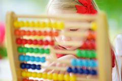 Cute little girl playing with abacus at home. Smart child learning to count. Cute little girl playing with wooden abacus at home. Smart child learning to count royalty free stock photo