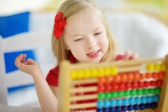 Cute little girl playing with abacus at home. Smart child learning to count. Cute little girl playing with wooden abacus at home. Smart child learning to count stock photo