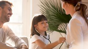 Cute playing doctor visiting pediatrician while doctor and dad laughing. Cute little girl playing as doctor visiting pediatrician while doctor and dad laughing stock image