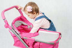 Cute little girl playing with baby stroller Stock Photos