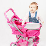 Cute little girl playing with baby stroller Royalty Free Stock Photography