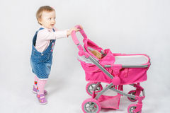 Cute little girl playing with baby stroller Stock Images