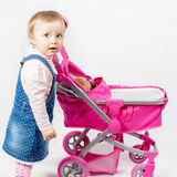 Cute little girl playing with baby stroller Stock Photography