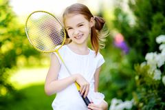 Cute little girl playing badminton outdoors. On warm and sunny summer day Stock Photos