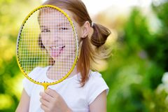Cute little girl playing badminton outdoors. On warm and sunny summer day Royalty Free Stock Photo