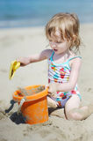 Cute little girl playing on a beach. Cute little girl playing with beach toys on a beach Royalty Free Stock Photography