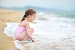 Cute little girl playing on a beach. Cute little girl playing jumping over the waves Stock Photography