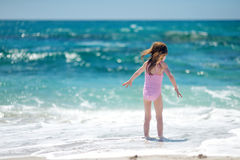 Cute little girl playing on a beach. Cute little girl playing jumping over the waves Stock Photos