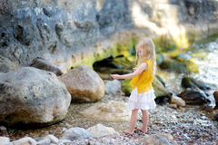 Cute little girl playing on a beach of lake Garda on warm and sunny summer day Royalty Free Stock Image
