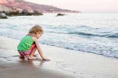Cute little girl playing on the beach Stock Images