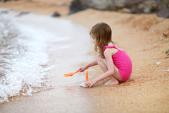 Cute little girl playing on a beach. Cute little girl playing with beach toys on a beach Royalty Free Stock Photo