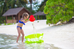 Cute little girl playing with beach toys during Stock Photography
