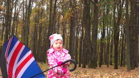 Cute little girl playing with British flag-like umbrella in autumn park. Bad weather concept. 4K steadicam shot stock video footage