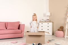 Cute little girl playing with cardboard box royalty free stock image