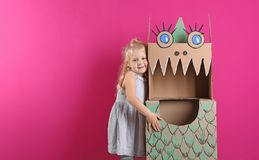 Cute little girl playing with cardboard dragon on color background. royalty free stock photos