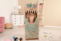 Cute little girl playing with cardboard dragon royalty free stock photos