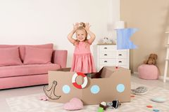 Cute little girl playing with cardboard ship royalty free stock images