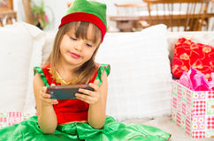 Cute little girl playing with cell phone at a Royalty Free Stock Images