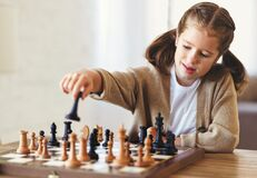 Cute Little Girl Playing Chess While Spending Leisure Time At Home During During Day Time Royalty Free Stock Photo