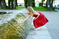 Cute little girl playing with a city fountain on hot and sunny summer day royalty free stock image
