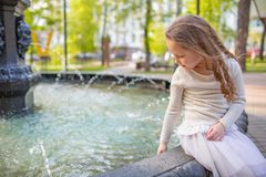 Cute little girl playing by city fountain on hot and sunny summer day. Child having fun with water in summer. Active leisure for k stock images