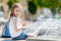 Cute little girl playing with a city fountain. Cute little preschooler girl playing with a city fountain on hot and sunny summer day royalty free stock images