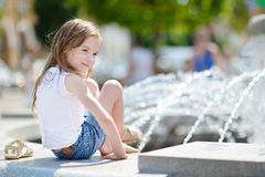 Cute little girl playing with a city fountain Royalty Free Stock Photography