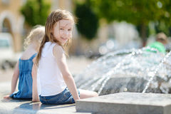 Cute little girl playing with a city fountain Stock Photography