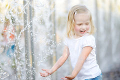 Cute little girl playing with a city fountain. Cute little preschooler girl playing with a city fountain on hot and sunny summer day stock images