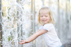 Cute little girl playing with a city fountain Stock Photo
