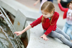 Cute little girl playing with a city fountain Royalty Free Stock Photos
