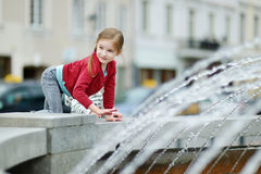 Cute little girl playing with a city fountain Stock Image