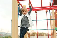 Cute little girl playing on climbing net at school yard playground. Kid play and climb outdoors. Happy child playing at preschool stock photos