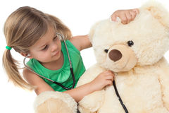 Cute little girl playing doctor with her teddy bear Stock Photo