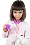 Cute little girl playing doctor with teddy Stock Image