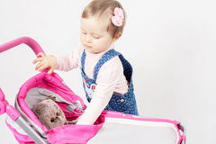 Cute little girl playing with doll and baby stroller Royalty Free Stock Images