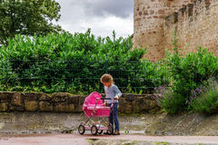 Cute little girl playing with doll and babycarrier in the park Royalty Free Stock Images