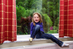 Cute little girl playing with drapes on the window. Marble  sill Stock Images