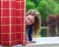 Cute little girl playing with drapes on the window Stock Images