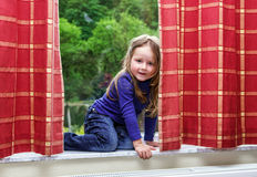 Cute little girl playing with drapes on the window. Marble  sill Royalty Free Stock Image