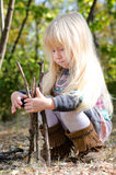 Cute Little Girl Playing with Dry Sticks Stock Image