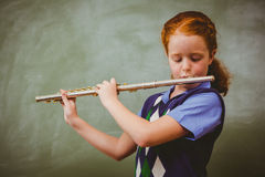 Cute little girl playing flute in classroom Stock Photo