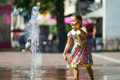 Cute little girl playing with fountain splash Stock Images