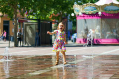 Cute little girl playing with fountain splash Royalty Free Stock Image