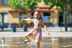 Cute little girl playing with fountain splash Royalty Free Stock Photography