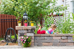 Cute little girl playing on a garden wall Royalty Free Stock Image