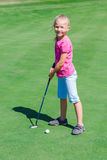 Cute little girl playing golf on a field Stock Images