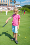 Cute little girl playing golf on a field outdoor Stock Images