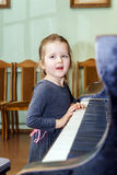Cute little girl playing grand piano Stock Photo